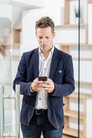 Fashionable business professional at office door using his mobile phone Foto de archivo - 122337699