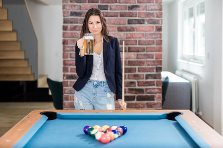 Beautiful female billiard player holding beer mug next to pool table.