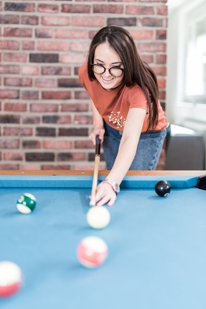 Fashionable urban woman playing pool table billiards game. Foto de archivo - 122337703