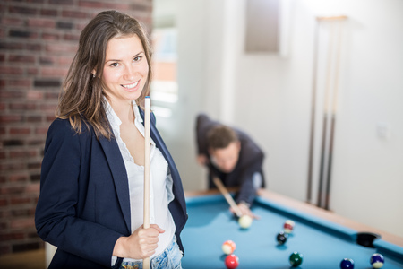 Portrait of beautiful billiard female player holding a cue stick and fashionable man aiming the ball at the pool table. Foto de archivo - 122337704