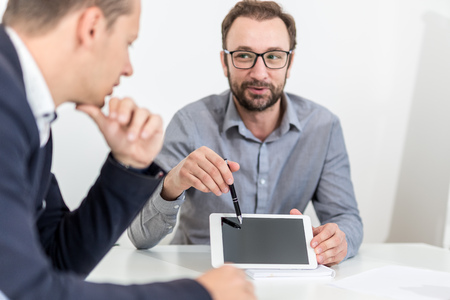 Businessman presenting something on blank screen digital tablet to his colleague on a meeting. Foto de archivo - 122337709