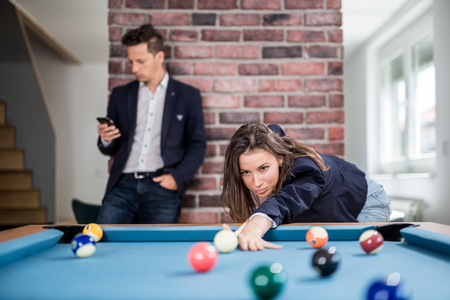 Fashionable woman playing billiard game while man using his smartphone in the background. Foto de archivo - 122337710