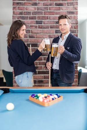 Couple cheering with beer next to billiard pool table. Foto de archivo - 122337786