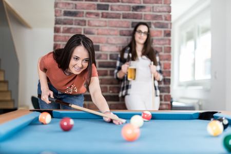 Two female students playing billiard game and drinking beer. Foto de archivo - 122337790
