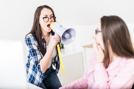 Businesswoman shouting at her colleague by using megaphone at the office. Foto de archivo - 122337798