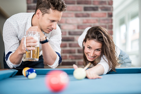 Couple playing snooker game and drinking beer. Foto de archivo - 122812874