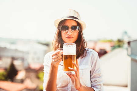Portrait of happy woman holding mug of beer outside on sunny day. Selective focus.