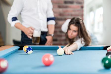 Fashionable couple playing pool table billiard game in office chill room. Foto de archivo - 122812883