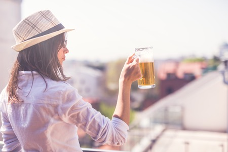 Young woman holding beer drinking glass outdoors. Foto de archivo - 122812885