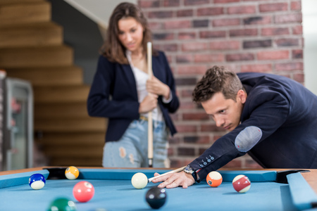 Young modern couple playing pool table billiard game. Foto de archivo - 122812887
