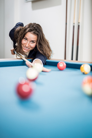 Portrait of beautiful young female playing billiards. Space for copy. Foto de archivo - 122812892