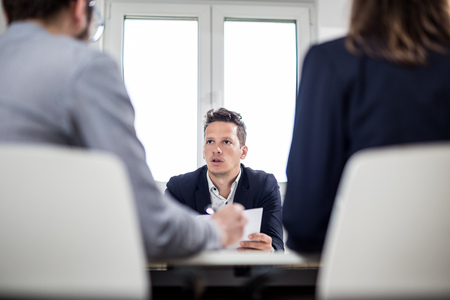 Portrait of young businessman discussing with his colleagues at the desk in meeting or conference room. Foto de archivo - 122812902