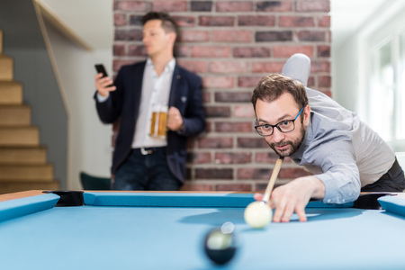 Business guys playing pool table billiard game in office chill room. Foto de archivo - 122812912