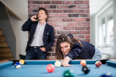 Fashionable woman playing billiard game while man talking on smartphone in the background. Foto de archivo - 122812914