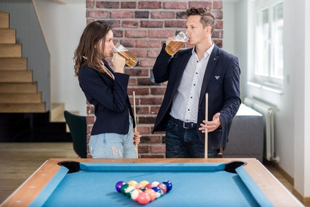Couple drinking beer next to billiard pool table. Foto de archivo - 122812915