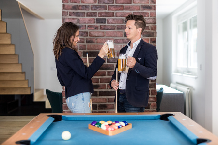 Couple cheering with beer next to billiard pool table. Foto de archivo - 122813165