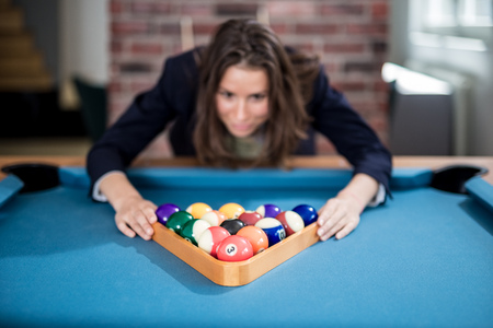 Portrait of young fashionable woman holding triangle wooden rack with pool balls on billiard table.
