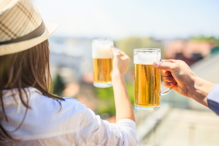 Rear view of hipster woman and man holding beer mugs outdoors. Foto de archivo - 122813169