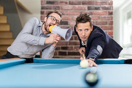 Billiard player aiming the ball while his friend disturbing him by using megaphone. Foto de archivo - 122813170
