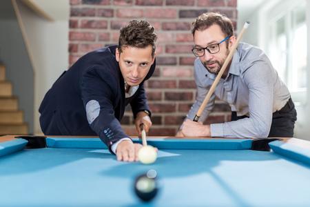 Two fashionable men friends playing billiard game. Foto de archivo - 122813171