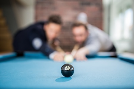 Two fashionable men friends aiming black pool ball. Foto de archivo - 122813174