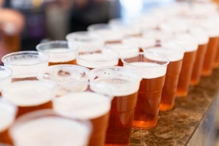 Bar counter full of beer in plastic glasses. 版權商用圖片