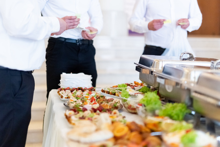 Canapes served on buffet table and waiters in the background.