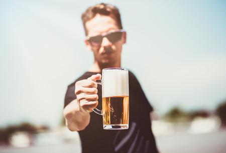 Man holding mug of beer outdoors. Banco de Imagens