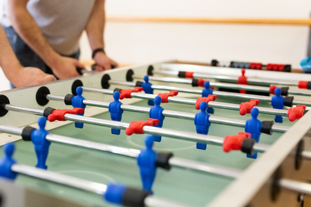 Young people playing foosball indoors.