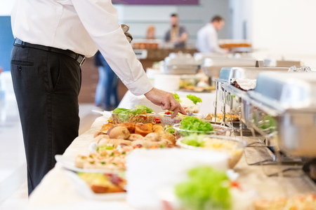 Waiter preparing buffet table with canapes and salads with vegetables. Banco de Imagens