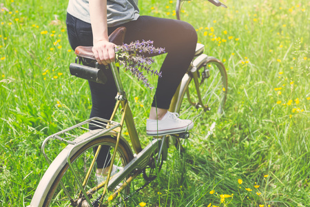Rear view of female on bicycle holding bouquet of flowers in the field. Stock Photo