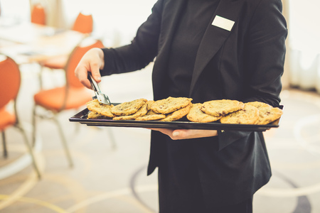 Close up of waitress holding a plate with fresh homemade cookies.
