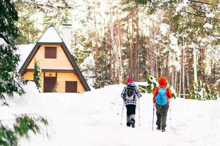 Rear view of two hikers coming back to their cottage. Winter scene.