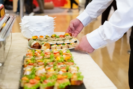 Close up of waiter hands serving canapes on buffet table. 스톡 콘텐츠