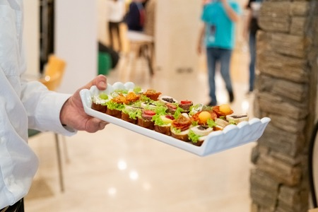 Close up of waiter holding platter with colorful canapes indoors. Banco de Imagens