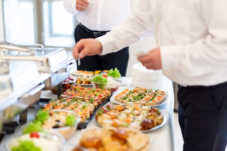 Waiters preparing buffet canape food table.