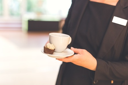 Close up of waitress holding cup of coffee and small cookie. Space for copy. Imagens