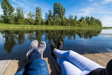 Couple sitting on pier against beautiful nature. Feet close up.