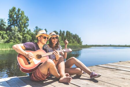 Young fashionable couple playing acoustic guitar while sitting on wooden dock against beautiful lake and trees. Summer concept.