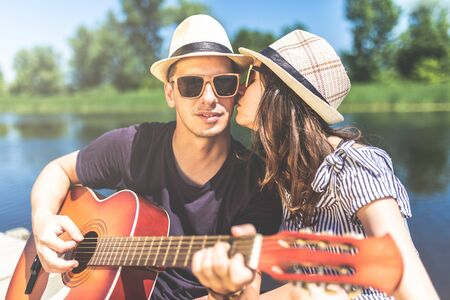 Young musician with acoustic guitar with his girlfriend kissing him against beautiful nature in the background. Love and music concept.