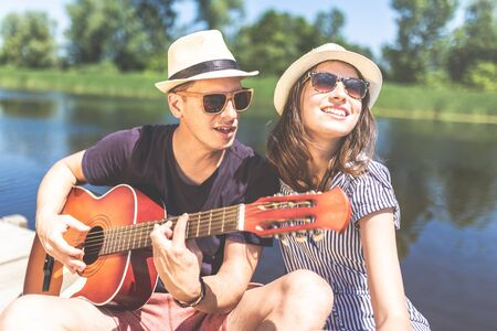 Young couple playing acoustic guitar and singing their favorite song in nature. Love and music concepts.
