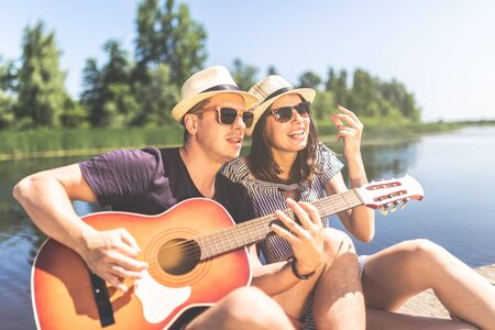 Young couple in love singing their favorite song and playing guitar against beautiful nature.