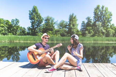 Beautiful couple sitting on pier with acoustic guitar and singing song. Love, music and nature concepts. Stock Photo