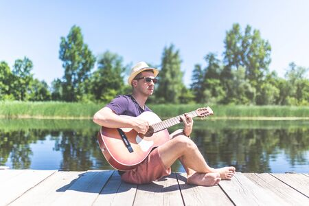 Modern fashionable man sitting on wooden pier and playing acoustic guitar with beautiful lake in the background. Music and vacation concepts. Stock Photo