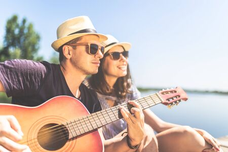 Beautiful fashionable couple with acoustic guitar against lake or river in the background. Summer and relationship concept. Imagens