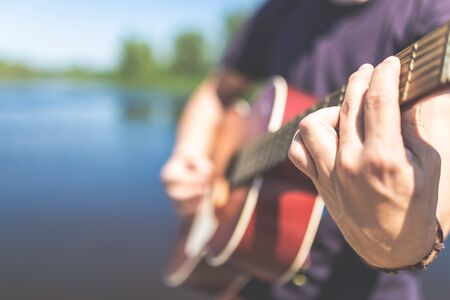 Man hands holding acoustic guitar in nature. Music and summer concepts.
