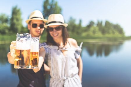 Young couple holding beer glasses against beautiful nature in the background. Summer and travel concepts.