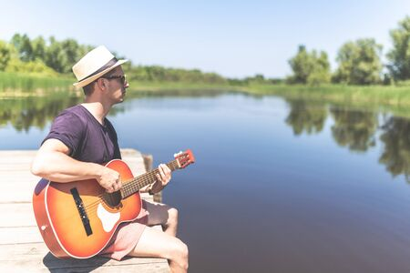 Side view of modern man sitting at pier edge, playing guitar and enjoying beautiful nature. Space for copy. Stock Photo
