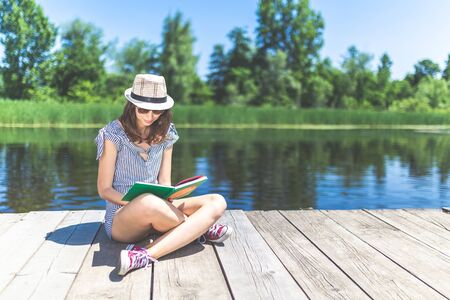 Young beautiful woman sitting on pier and reading book. Beautiful nature in the background. Space for copy.