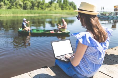 Young woman sitting on wooden pier with hands on her blank screen laptop against two man in boat. Nature and freelance concepts.